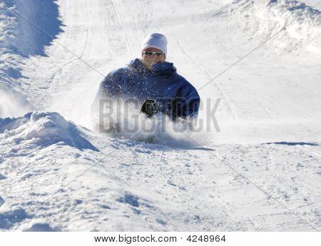 Man Braking While Sledding Down The Hill