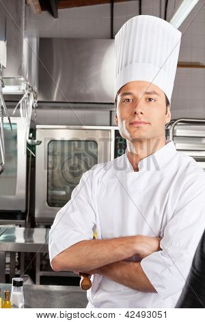 Portrait of confident male chef standing with arms crossed in commercial kitchen