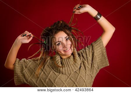 Portrait Of A Beautiful Young Woman With Dreadlocks On A Red