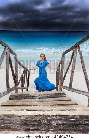 The woman in a long blue dress goes on the stormy sea coast
