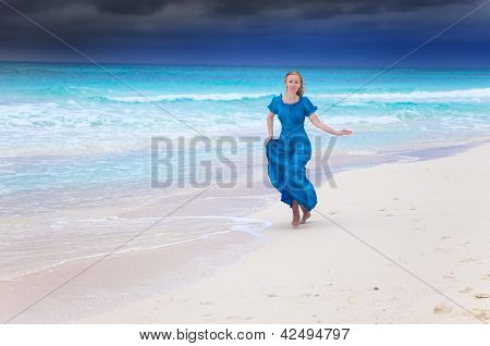 The woman in a long blue dress run in a surf of stormy sea