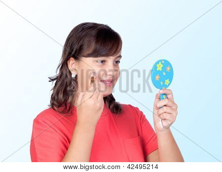 Beautiful girl makeup in front of a mirror isolated on blue background
