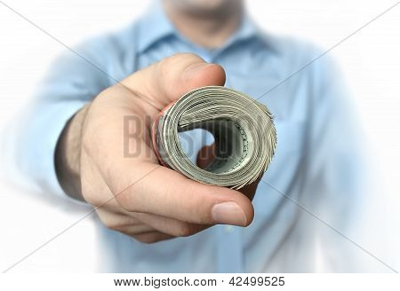 A roll of dollars in hand