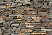 stock photo of slab  - newly built dry stone wall architectural feature wall on large building good for backgrounds or wallpaper - JPG