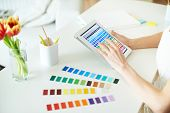 Female designer working with colors in touchpad