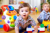 stock photo of indoor games  - curious baby boy studying colorful nursery room - JPG