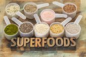 stock photo of flax seed  - superfoods word in letterpress wood type with plastic scoops of healthy seeds and powders  - JPG