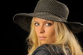 picture of poka dot  - Beautiful blonde woman with spotted hat and denim jacket looking over shoudler with black background - JPG