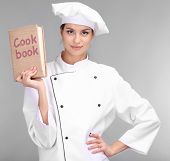 Portrait of young woman chef with cookbook on grey background