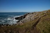foto of anglesey  - The Wales coast path leads across the point at Cable bay Anglesey Wales UK with rocks leading to the sea and a small figure of a man looking out - JPG