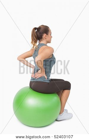 Blonde pony tailed woman touching her back sitting on fitness ball
