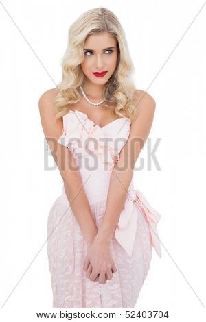 Concentrated blonde model in pink dress posing holding her hands and looking away on white background