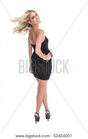 Smiling blonde woman posing looking over shoulder on white background