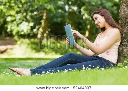 Happy woman leaning against a tree working with her tablet on a sunny day