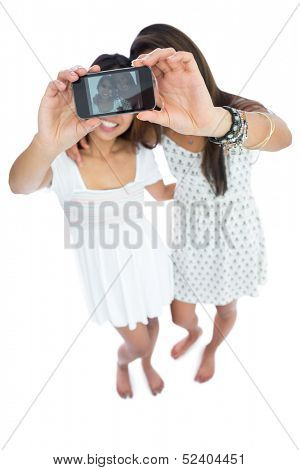 Two cute asian sisters taking a self portrait on white background