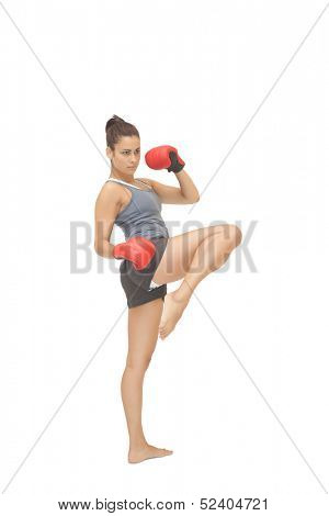 Concentrating sporty brunette kick boxing on white background