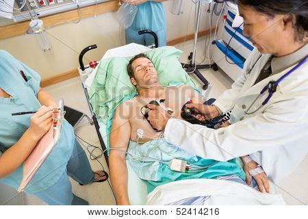 High angle view of doctor defibrillating male patient while nurses standing by in hospital