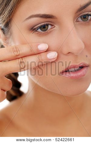 Portrait of a beautiful girl with a plait who is touching herself and posing over a white background