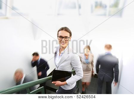 Portrait of smart businesswoman looking at camera on background of other people ascending and descending staircase
