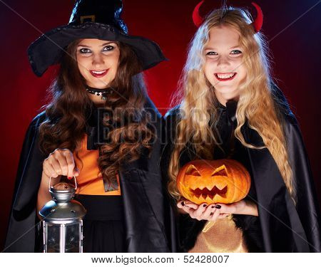 Portrait of two happy females with lantern and pumpkin looking at camera with smiles