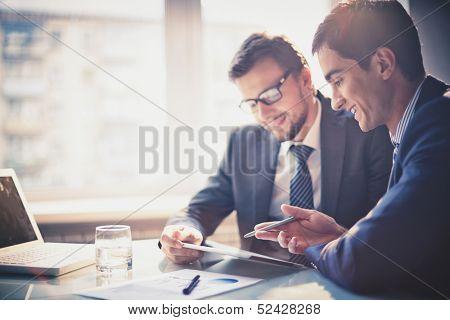 Imagen de dos jóvenes empresarios con touchpad en reunión