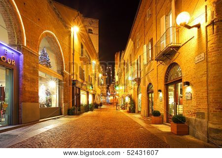 ALBA - DECEMBER 07: Popular touristic street in old city historic center with opened shops, bars and stores illuminated for Christmas and New Year holidays in Alba, Italy on December 07, 2011.