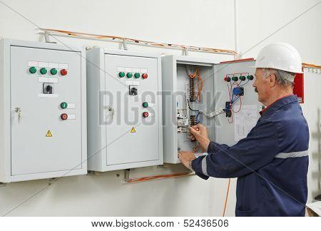 senior adult electrician builder engineer testing equipment in fuse box