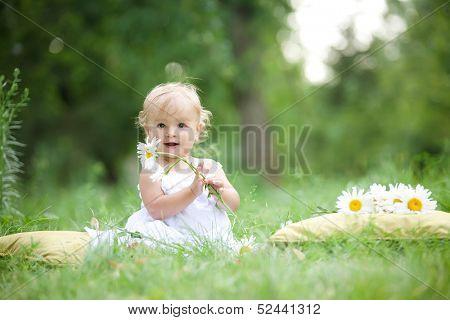 baby sitting on green grass