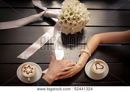Man and woman's hands and coffee cups on the table