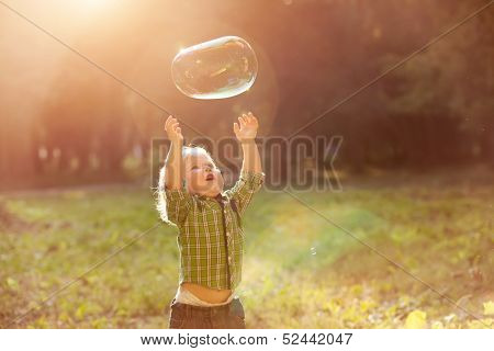 little boy in the sunset catches soap bubbles