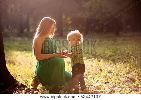 pregnant mother and her little son in the park at sunset
