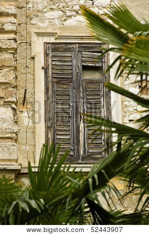 Tipical old window in mediterran area with palms