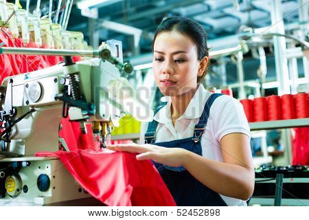Seamstress or worker in a factory sewing with a industrial sewing machine, she is very accurate