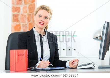 Young female lawyer working in her office with a typical law book and writing in a document