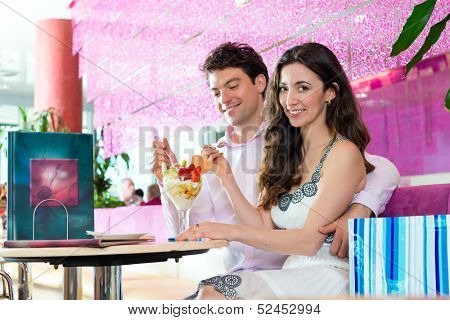 Young Couple in a Cafe or Ice cream parlor, eating together an ice cream sundae