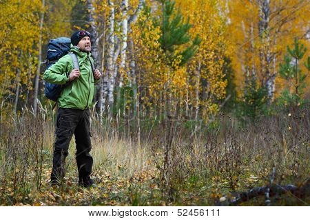 Full lenght portrait of the mature backpacker in an autumn forest