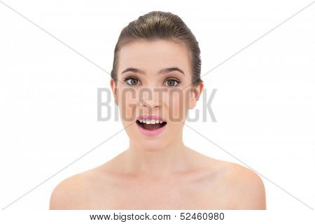 Astonished natural brown haired model looking at camera on white background