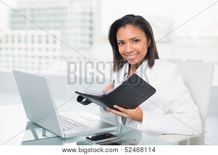 Natural young dark haired businesswoman filling her schedule in bright office