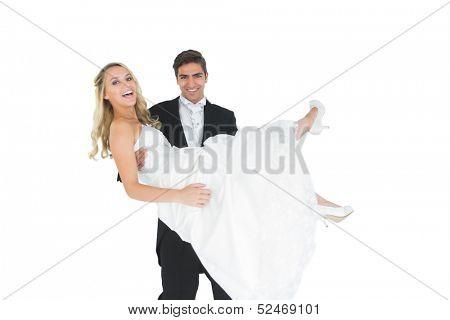 Smiling bridegroom lifting his wife up smiling at camera