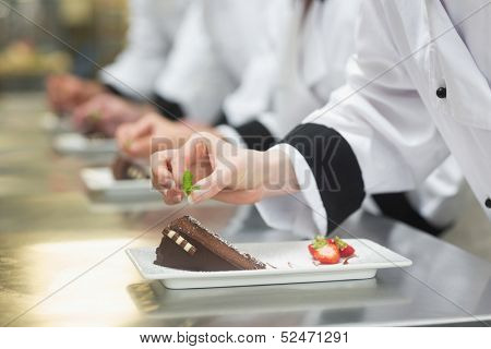 Team of chefs in a row garnishing dessert plates in a busy kitchen