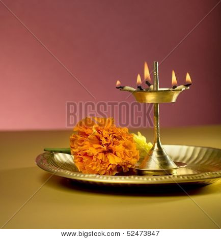 Indian lamp and marigold flower in a plate