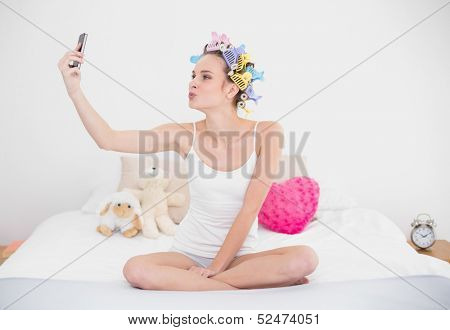 Playful natural brown haired woman in hair curlers taking a picture of herself with mobile phone in bright bedroom