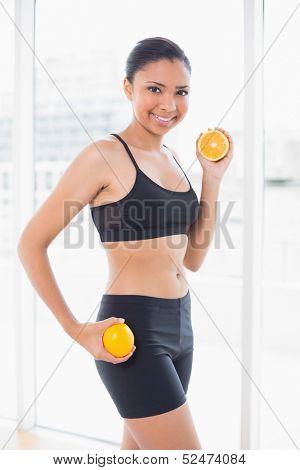 Dynamic dark haired model in sportswear holding orange halves in bright fitness studio