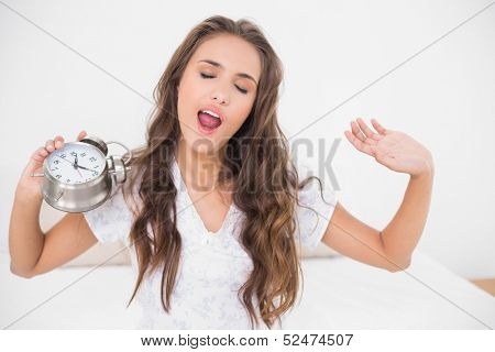 Yawning brunette holding alarm clock in bright bedroom