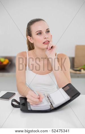 Thoughtful young woman writing in a planner in the kitchen at home