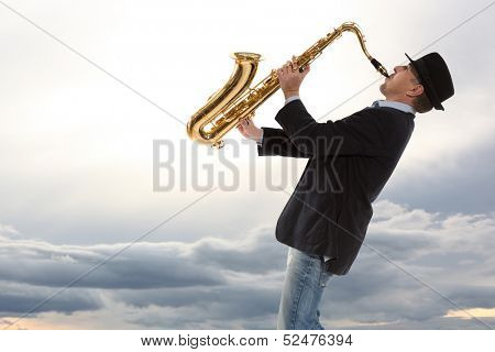 Saxophonist. Man playing on saxophone against the background of sky