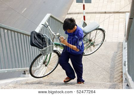 young boy carry bicycle by hand