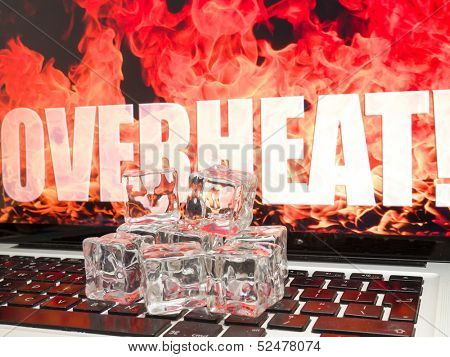 Ice cubes on computer keyboard with flames on background OVERHEAT
