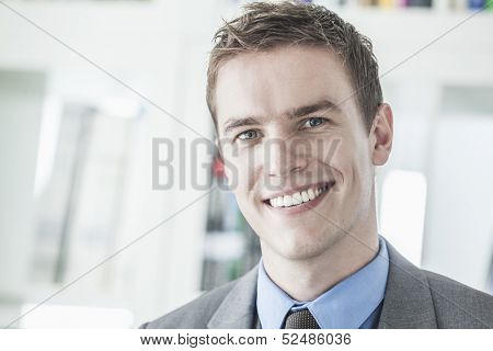 Portrait of young smiling businessman looking at camera