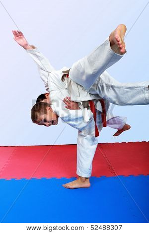 Small athlete with a white belt performs throw judo